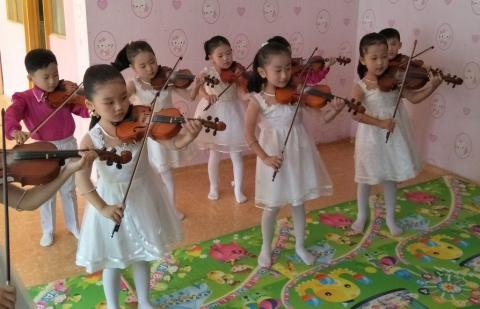 Children aged 4 to 6 paying violins
